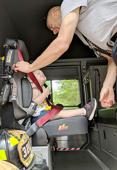 Firefighter helping a toddler sit in a fire truck during a community event