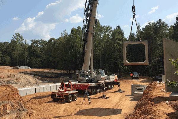 A crane lowers a culvert into place
