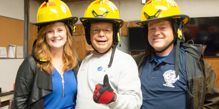 three fire academy attendees wearing helmets and giving the thumbs up