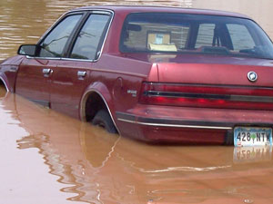 A red car half submerged in water due to a flood